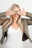 Junge blonde Frau, die ihre Augen bedeckt Lizenzfreie Stockfotos