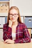 Junge blonde Frau, die in ihrem Büro sitzt Lizenzfreies Stockfoto