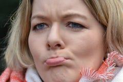Junge blonde Frau, die ihren Mund skeptisch schürzt Lizenzfreie Stockfotos