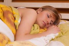 Junge blonde Frau, die im Bett schläft Lizenzfreie Stockbilder