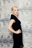Junge blonde Frau, die im schwarzen Kleid aufwirft Stockfotos