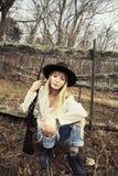 Junge blonde Frau, die im Wald mit einem Gewehr stationiert Stockfotos