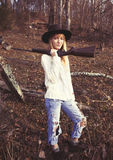 Junge blonde Frau, die im Wald mit einem Gewehr stationiert Lizenzfreie Stockfotos