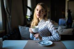 Junge blonde Frau, die Kaffeezeit im Café genießt Stockfotografie
