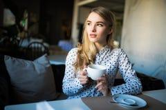 Junge blonde Frau, die Kaffeezeit im Café genießt Stockbilder