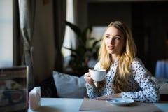 Junge blonde Frau, die Kaffeezeit im Café genießt Lizenzfreies Stockfoto