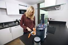 Junge blonde Frau, die Karotten auf Schneidebrett in der Küche hackt Lizenzfreie Stockfotos