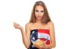 Junge blonde Frau, die Kartoffelchips in einer transparenten Platte lokalisiert auf einem weißen Hintergrund hält Lizenzfreies Stockbild