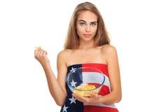 Junge blonde Frau, die Kartoffelchips in einer transparenten Platte lokalisiert auf einem weißen Hintergrund hält Stockfotografie