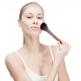 Junge blonde Frau, die Kosmetikbürste auf Weiß hält Stockbilder