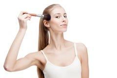Junge blonde Frau, die Kosmetikbürste auf Weiß hält Lizenzfreie Stockfotos