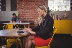 Junge blonde Frau, die Laptop beim Sitzen an der Kaffeestube verwendet Lizenzfreie Stockfotos