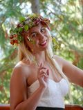 Junge blonde Frau, die mit Autumn Leaves Crown auf Kopf lächelt Stockbild