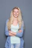 Junge blonde Frau, die mit den Armen gekreuzt lächelt Lizenzfreie Stockfotos