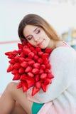 Junge blonde Frau, die mit einem Blumenstrauß von roten Tulpen lächelt lizenzfreies stockfoto