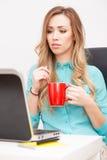 Junge blonde Frau, die mit einem Laptop arbeitet Stockfotos
