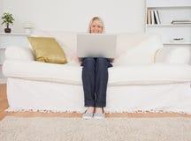 Junge blonde Frau, die mit einem Laptop auf einem sof sich entspannt Lizenzfreies Stockbild