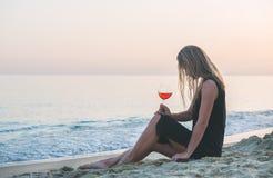 Junge blonde Frau, die mit Glas rosafarbenem Wein auf Strand durch das Meer bei Sonnenuntergang sich entspannt Lizenzfreies Stockbild