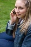 Junge blonde Frau, die mit ihrem Handy beim Sitzen von i nennt Lizenzfreie Stockfotos