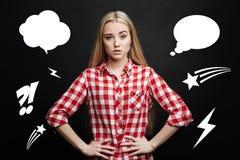 Junge blonde Frau, die mit ihren Händen auf Hüften steht und interessiert schaut Stockbilder