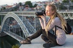Junge blonde Frau, die mit Kamera nahe Brücke Dom Luiss I über dem Duero-Fluss in Porto sitzt Stockfotografie