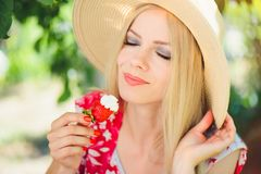 Junge blonde Frau, die mit Sahne Erdbeeren, glücklich im Garten an einem sonnigen Tag des Sommers, tonisches Bild des warmen Somm Stockbilder