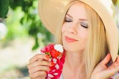 Junge blonde Frau, die mit Sahne Erdbeeren, glücklich im Garten an einem sonnigen Tag des Sommers, tonisches Bild des warmen Somm Stockfoto