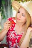Junge blonde Frau, die mit Sahne Erdbeeren, glücklich im Garten an einem sonnigen Tag des Sommers, tonisches Bild des warmen Somm Stockfotos