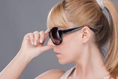 Junge blonde Frau, die modernes sunglasse anhält Lizenzfreie Stockfotografie