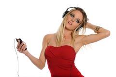 Junge blonde Frau, die Musik hört Stockbilder