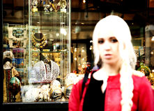Junge blonde Frau, die nahe bei einem Souvenirladen auf dem alten AR steht Stockfoto