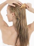 Junge blonde Frau, die nasses Haar kämmt Stockbilder