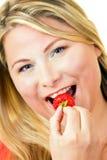 Junge blonde Frau, die reife Erdbeere isst Lizenzfreies Stockbild