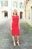 Junge blonde Frau, die rotes Kleid trägt Stockfotos