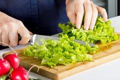 Junge blonde Frau, die Salat in der Küche bildet Lizenzfreie Stockfotos