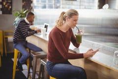 Junge blonde Frau, die Smartphone beim Trinken des Safts am Zähler verwendet Lizenzfreies Stockfoto