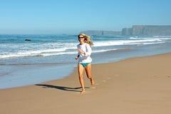 Junge blonde Frau, die am Strand rüttelt Lizenzfreie Stockfotografie