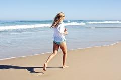 Junge blonde Frau, die am Strand rüttelt Lizenzfreie Stockbilder