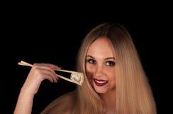 Junge blonde Frau, die Sushi isst Stockfoto
