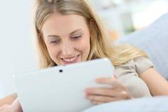 Junge blonde Frau, die Tablette verwendet Stockfoto