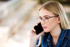 Junge blonde Frau, die am Telefon beim Sitzen im Freien spricht Lizenzfreies Stockfoto