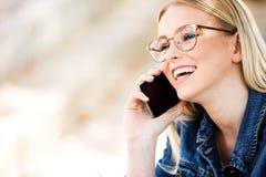 Junge blonde Frau, die am Telefon beim Sitzen im Freien spricht Lizenzfreie Stockbilder