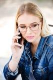 Junge blonde Frau, die am Telefon beim Sitzen im Freien spricht Stockfoto