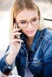 Junge blonde Frau, die am Telefon beim Sitzen im Freien spricht Lizenzfreie Stockfotos