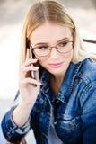 Junge blonde Frau, die am Telefon beim Sitzen im Freien spricht Stockbilder