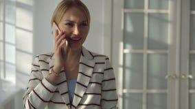 Junge blonde Frau, die am Telefon nahe bei einem großen Fenster spricht Stockbilder