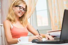 Junge blonde Frau, die vor Laptop sitzt und etwas schreibt Stockfotografie