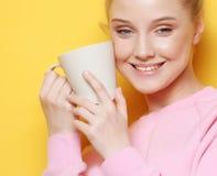Junge blonde Frau, die weiße Schale mit Tee oder Kaffee, Lebensstil und Lebensmittelkonzept hält Gelber Hintergrund Lizenzfreie Stockbilder