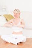 Junge blonde Frau, die Yoga im Wohnzimmer tut Stockbilder
