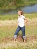 Junge blonde Frau draußen im Gras mit Wasser Lizenzfreie Stockfotos